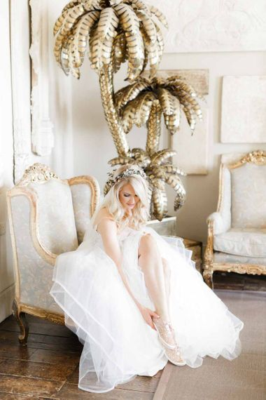 Bride puts on wedding shoes at whimsical wedding with Hayley Paige bride dress