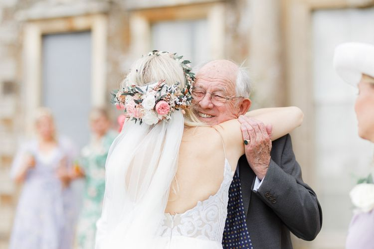 Bride wears flower crown and veil to greet guests