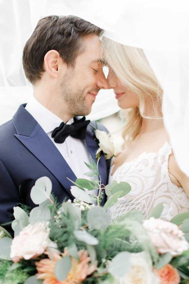 Lace detail bride dress with groom wearing tux and bowtie