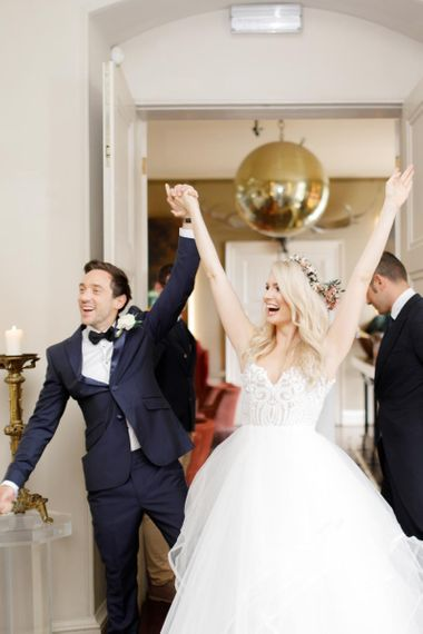 Bride and groom celebrate as they enter the wedding breakfast as husband and wife