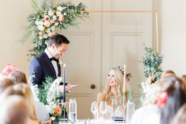 Groom makes a wedding speech with copper piping and flower decor