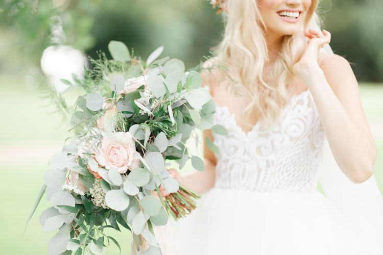 Bride with large flower and foliage bouquet at whimsical wedding