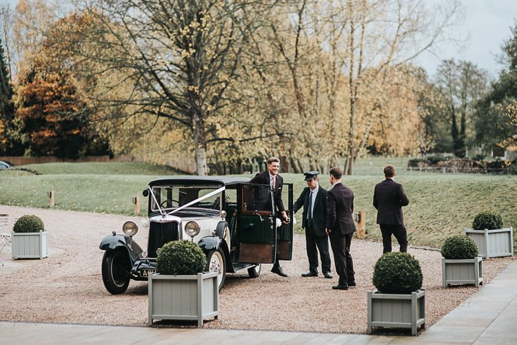 Groom in Moss Bros. Suit Getting Out of a Classic Wedding Car
