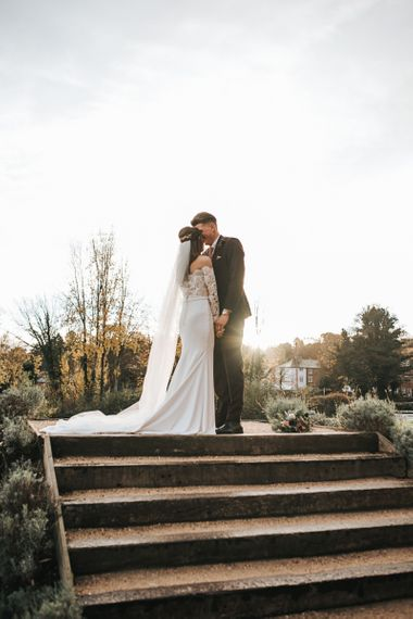 Bride in Pronovias Dracma Bardot Wedding Dress and Groom in Tailor Me Moss Bros. Suit Kissing
