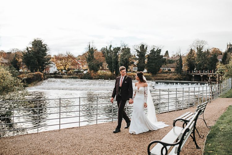 Bride in Lace Bardot Wedding Dress and Groom in Tailor Me Moss Bros. Suit Walking by the River Bank