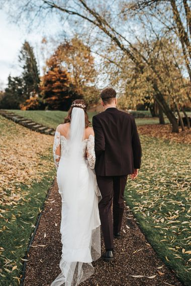 Bride in Lace Bardot Wedding Dress and Groom in Tailor Me Moss Bros. Suit Walking Through the Fallen Leaves