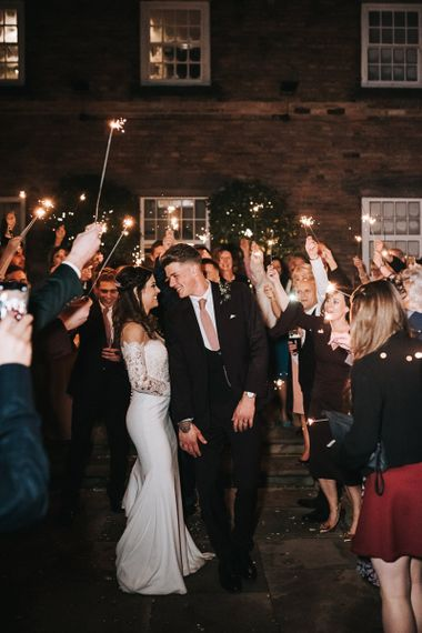 Sparkler Moment with Bride in Pronovias Dracma Bardot Wedding Dress and Groom in Tailor Me Moss Bros. Suit