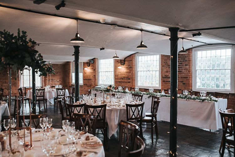 Wedding Reception Decor at Industrial Venue The West Mill in Derbyshire with Copper Centrepieces and Foliage Floral Arrangements