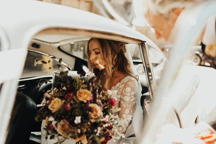Bride in vintage wedding car on her way to ceremony with bouquet