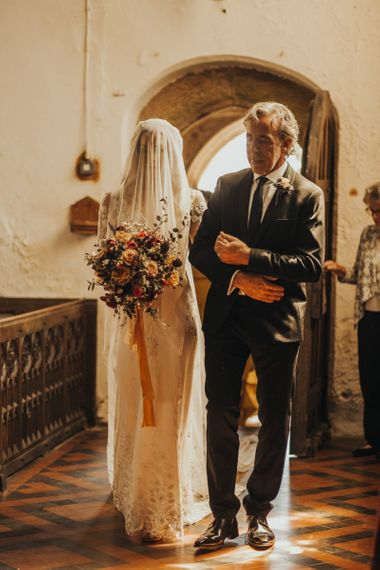 Bride enters church with traditional veil over face
