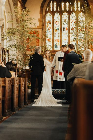 Bride and groom meet at altar with yellow bridesmaid dresses