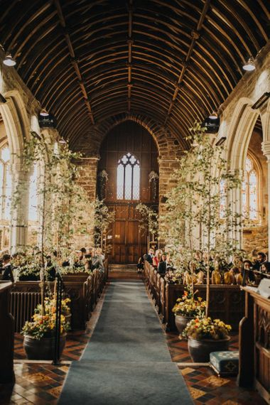 Tree decor lines the aisle for church wedding ceremony