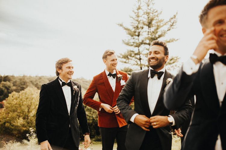Groom in red dinner jacket with groomsmen in tuxedos and yellow bridesmaid dresses
