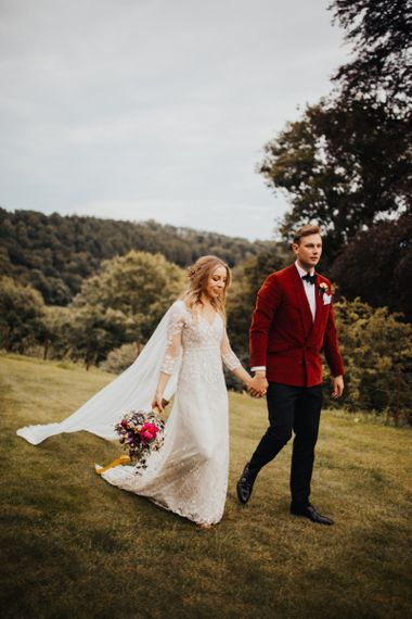 Bride in wedding cape holding a bouquet tied with yellow ribbon walking through their Devon venue with groom in a red velvet jacket