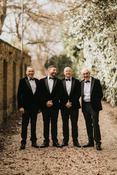 Groom and groomsmen in black tie tuxedo wedding suits