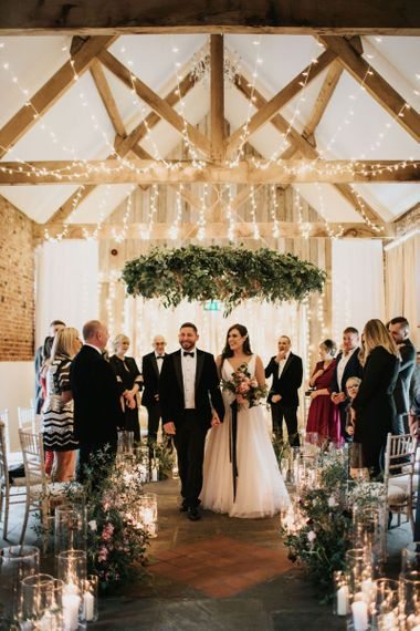 Foliage chandelier above newlyweds