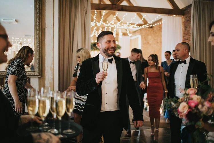 Groom enjoys a glass of champagne after Healing Manor wedding ceremony