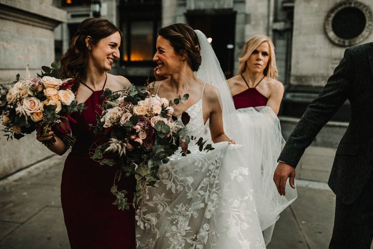 Bride in Lace Hayley Paige Wedding Dress and Bridesmaids in Burgundy Halter neck Dresses