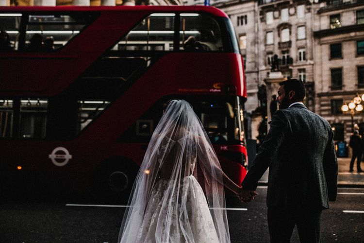 Bride in Fleur de lis Hayley Paige Wedding Dress with Open Back Detail and Cathedral Veil and Groom Holding Hands in London