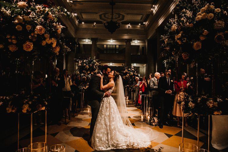 Bride in Fleur de lis Hayley Paige Wedding Dress  and Groom in Dark Suit Kissing at Jewish Blessing