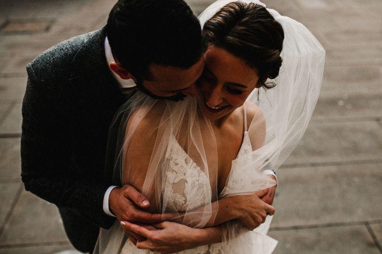 Bride in Hayley Paige Wedding Dress and Groom in Walker Slater Suit Embracing