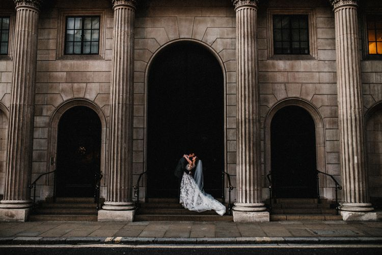 Bride in Hayley Paige Wedding Dress and Groom in Walker Slater Suit Kissing