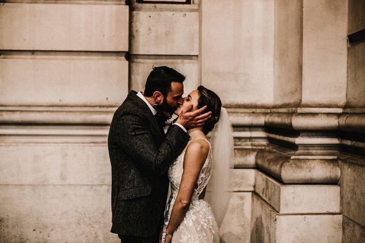Groom in Wool Walker Slater Three-piece Suit and Bride in Hayley Paige Wedding Dress Kissing