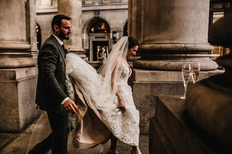 Groom in Wool Walker Slater Three-piece Suit Holding Up His Brides in Hayley Paige Wedding Dress Train