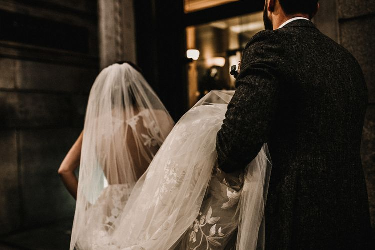 Groom in Wool Walker Slater Three-piece Suit Holding Up His Brides in Hayley Paige Wedding Dress Train and Veil