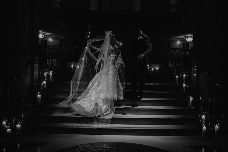 Bride in Hayley Paige Wedding Dress and Groom in Wool Walker Slater Suit Standing on a Candle Lit Staircase