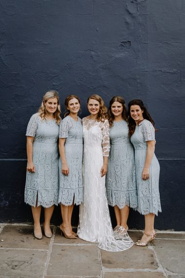 Bride in Embroidered Tulle Halfpenny London Dress with High Neckline, Batwing Sleeves and Low V-Back | Bridesmaids in Baby Blue Lace Dresses with Short Sleeves from Whistles | Floral Arch and Bride in Batwing Sleeve Halfpenny Dress for London Pub Wedding | Caitlin + Jones