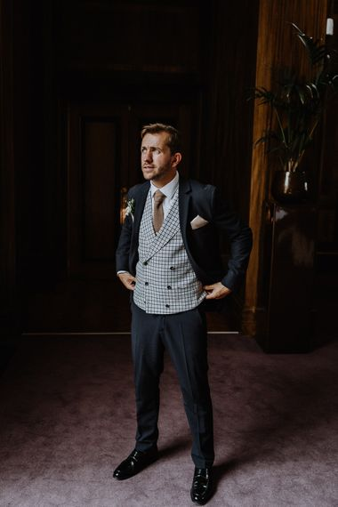 Groom in Navy Slim Fit Suit with Checked Double Breasted Waistcoat and Blush Pink Knitted Tie | Floral Arch and Bride in Batwing Sleeve Halfpenny Dress for London Pub Wedding | Caitlin + Jones