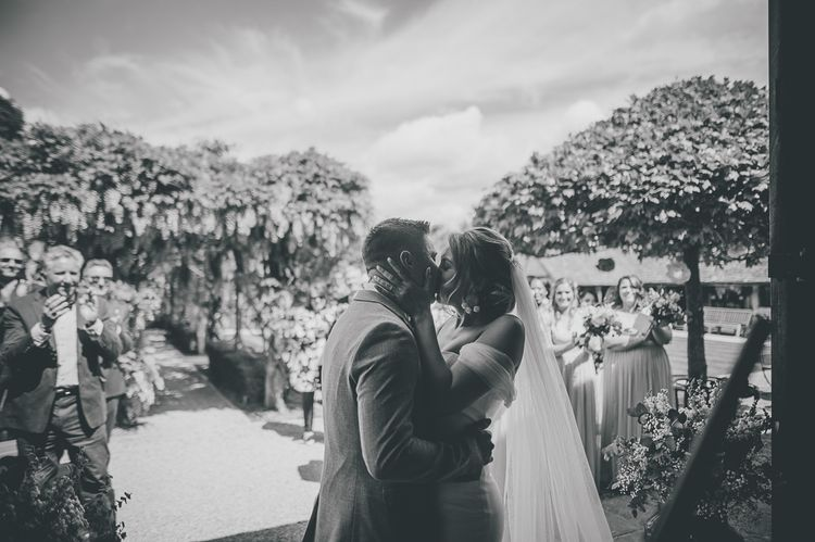 Bride kisses groom at outdoor rustic ceremony at Tythe Barn