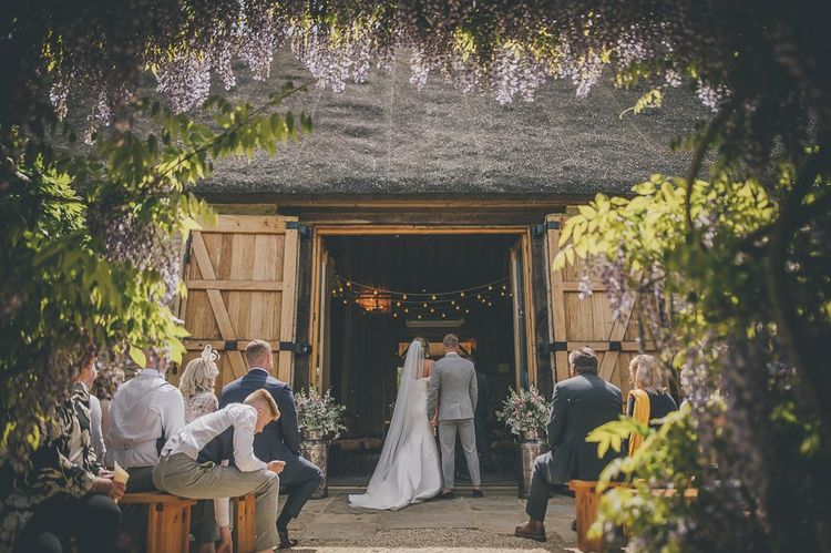 Stunning outdoor ceremony surrounded by purple wisteria at Tythe Barn