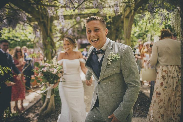 Confetti exit for bride in flat wedding shoes and groom in light suit with gypsophilia buttonhole