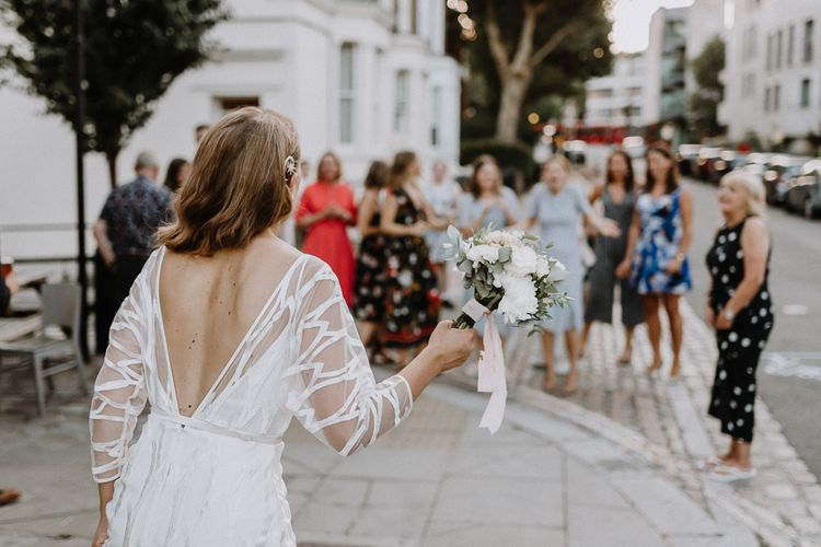Bride in Embroidered Tulle Halfpenny London Dress with High Neckline, Batwing Sleeves and Low V-Back | Anthropologie Hairpiece | Bridal Bouquet of White and Blush Pink Flowers with Eucalyptus and Trailing Silk Ribbon | Bouquet Toss | Floral Arch and Bride in Batwing Sleeve Halfpenny Dress for London Pub Wedding | Caitlin + Jones
