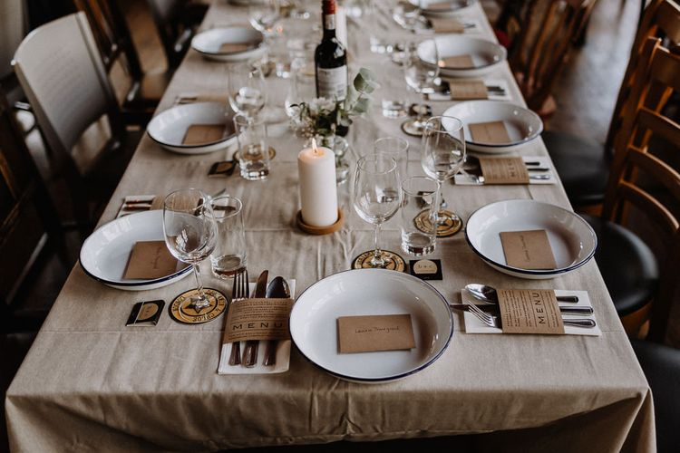 Kraft Paper Wedding Breakfast Menus | White Enamel Plates with Blue Rim | White Pillar Candle | Bud Vase with White Flowers and Eucalyptus | Banquet Table | Mismatched Chairs | Floral Arch and Bride in Batwing Sleeve Halfpenny Dress for London Pub Wedding | Caitlin + Jones