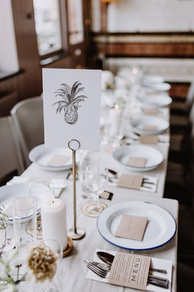 Hand Drawn Table Sign | White Enamel Plates with Blue Rim | White Pillar Candles | Kraft Paper Wedding Breakfast Menus | Banquet Table | Floral Arch and Bride in Batwing Sleeve Halfpenny Dress for London Pub Wedding | Caitlin + Jones