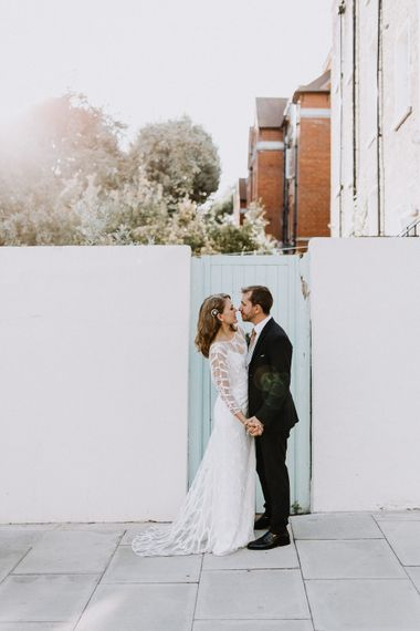 Bride in Embroidered Tulle Halfpenny London Dress with High Neckline, Batwing Sleeves and Low V-Back | Anthropologie Hairpiece | Groom in Navy Slim Fit Suit with Checked Double Breasted Waistcoat and Blush Pink Knitted Tie | Floral Arch and Bride in Batwing Sleeve Halfpenny Dress for London Pub Wedding | Caitlin + Jones