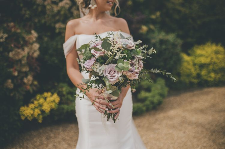Bride in flat wedding shoes in off-the-shoulder wedding dress and beautiful lilac bouquet