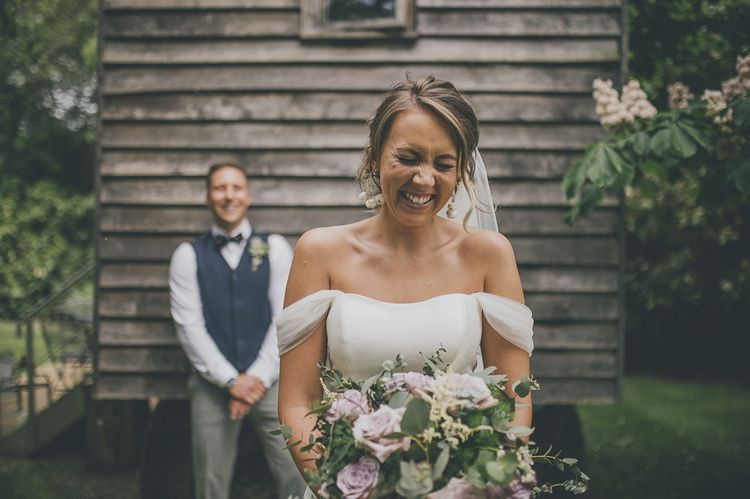 Bride in off the shoulder wedding dress and groom at Tythe Barn wedding venue