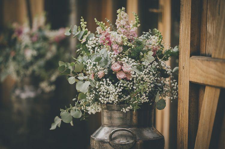 Rustic wedding flowers in milk churn for barn wedding