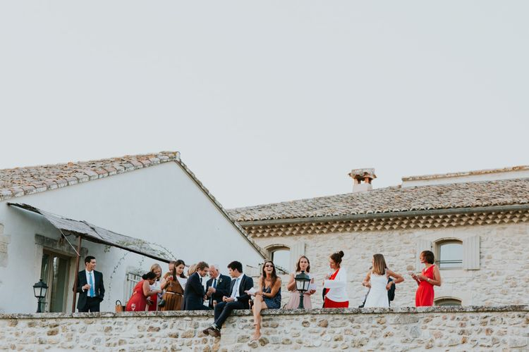 Wedding Guests Sitting on the Wall at Provence Wedding Venue