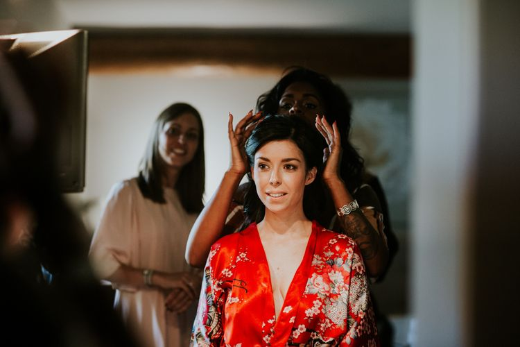Bride Having Her Wedding Hair and Makeup Done in Red Getting Robe