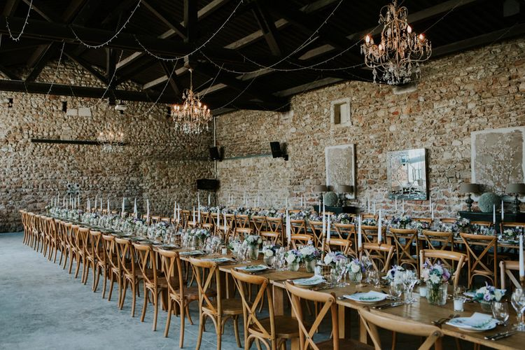 Barn Wedding Reception with Chandeliers, Wooden Table and Candle Sticks