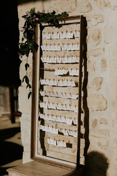 Escort Cards Pinned Up on Ornate Wedding Frame