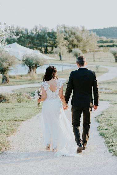 Bride in Appliqué Caroline Castigliano Wedding Dress and Groom in Tuxedo Walking Down a Country Lane