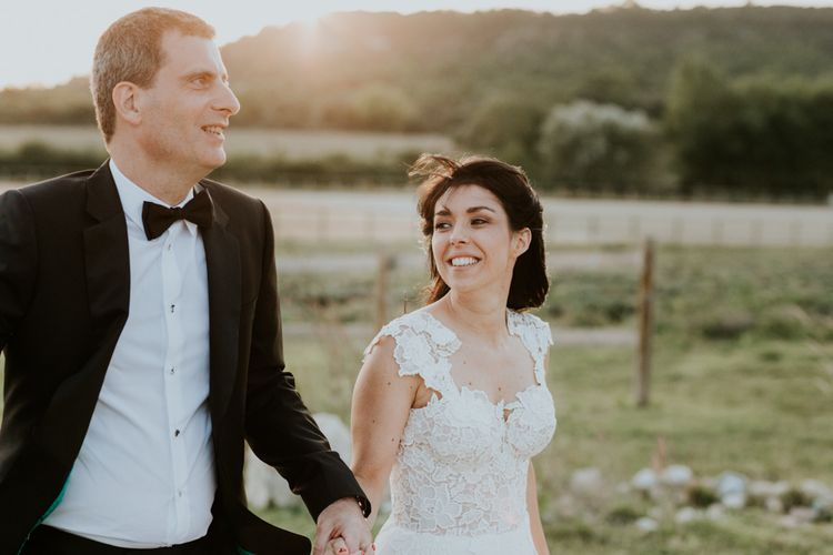 Golden Hour with Bride in Appliqué Caroline Castigliano Wedding Dress and Groom in Tuxedo Holding Hands