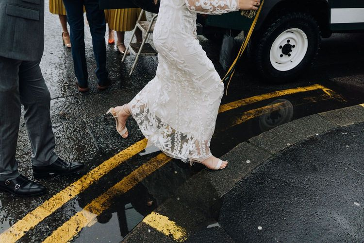 Bride in Phase Eight wedding dress stepping over puddle