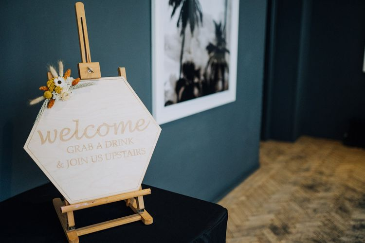 Hexagon wooden welcome sign on easel for minimalist yellow wedding theme